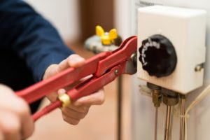 Plumber fixing the water heater using a wrench