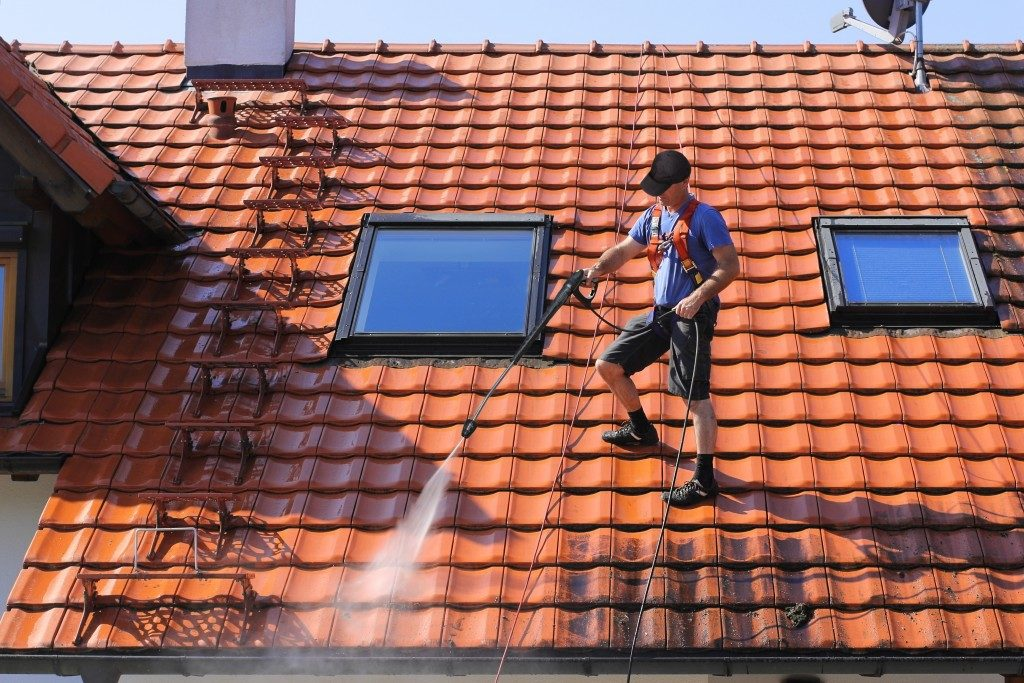 Man cleaning roof with high pressure water