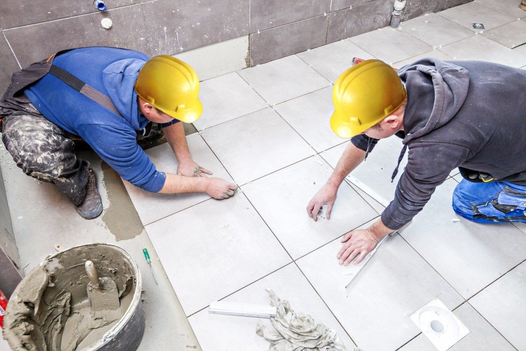 Workers placing tiles on the floor