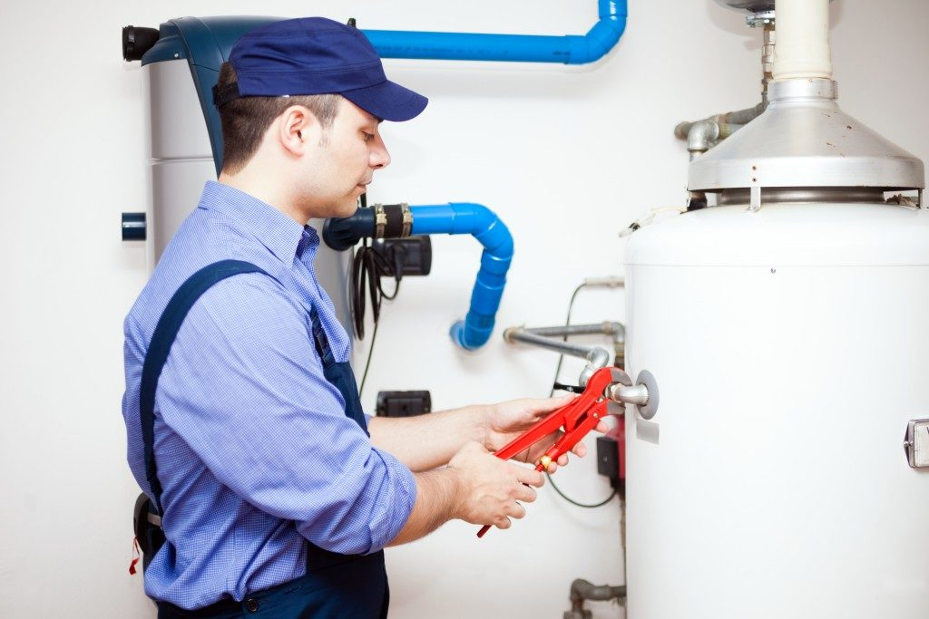 Plumber fixing the water heater