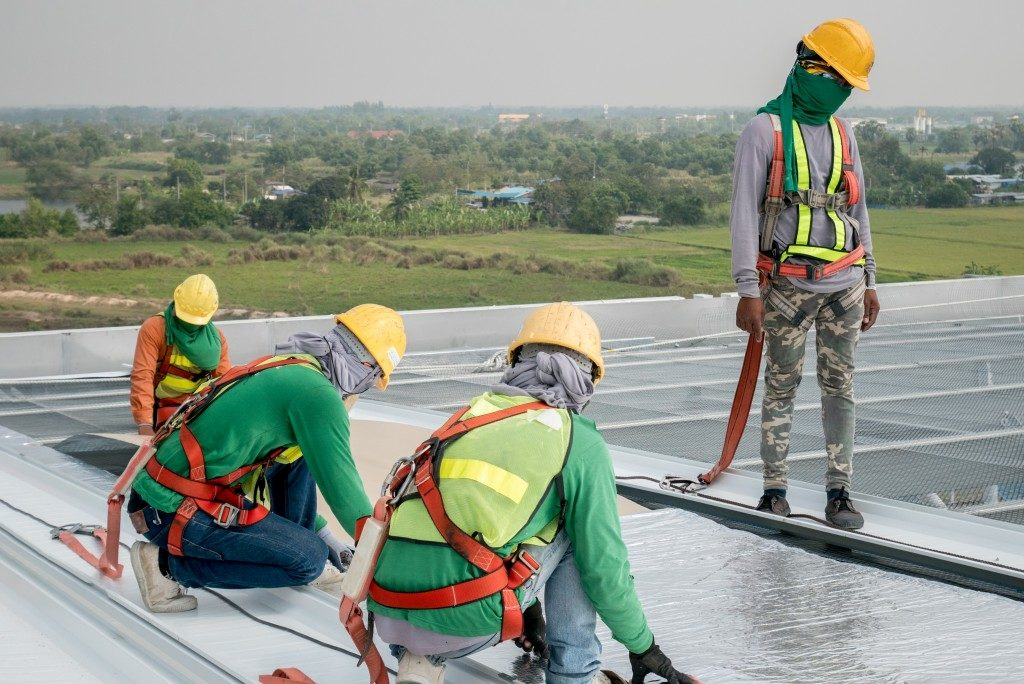 Workers fixing flat roof