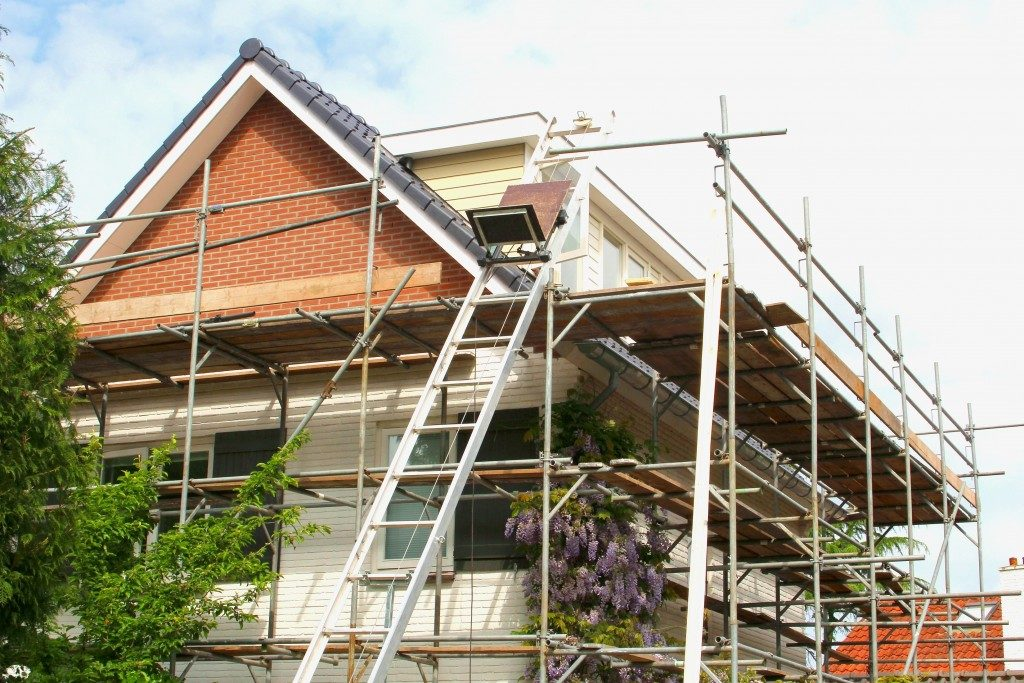 Exterior renovation of a modern house and construction equipments