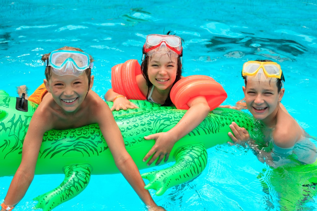Children inside the pool with floaters