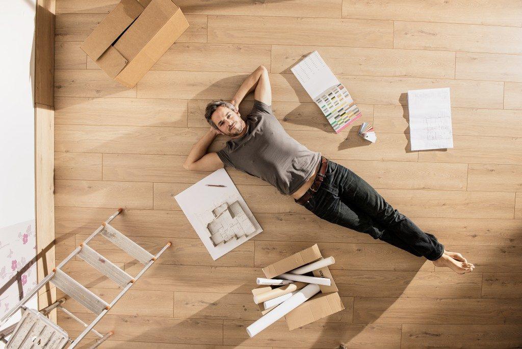 Man lying on the floor beside design materials