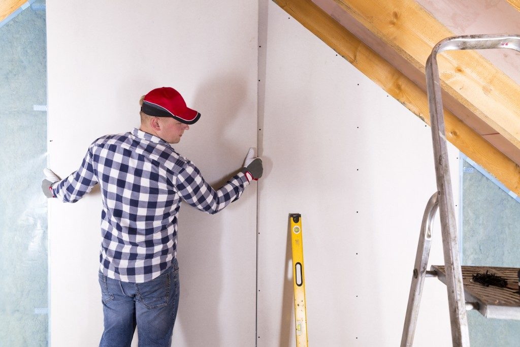 Worker installing a drywall