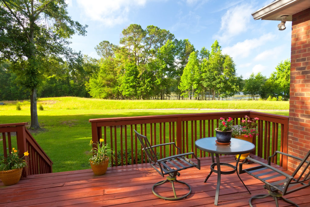 Wooden-deck-overlooking-a-green-field