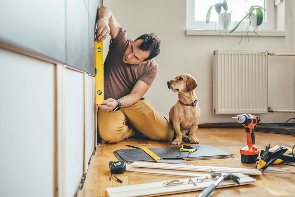 Man measuring wall with dog beside him