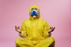 man wearing PPE meditating