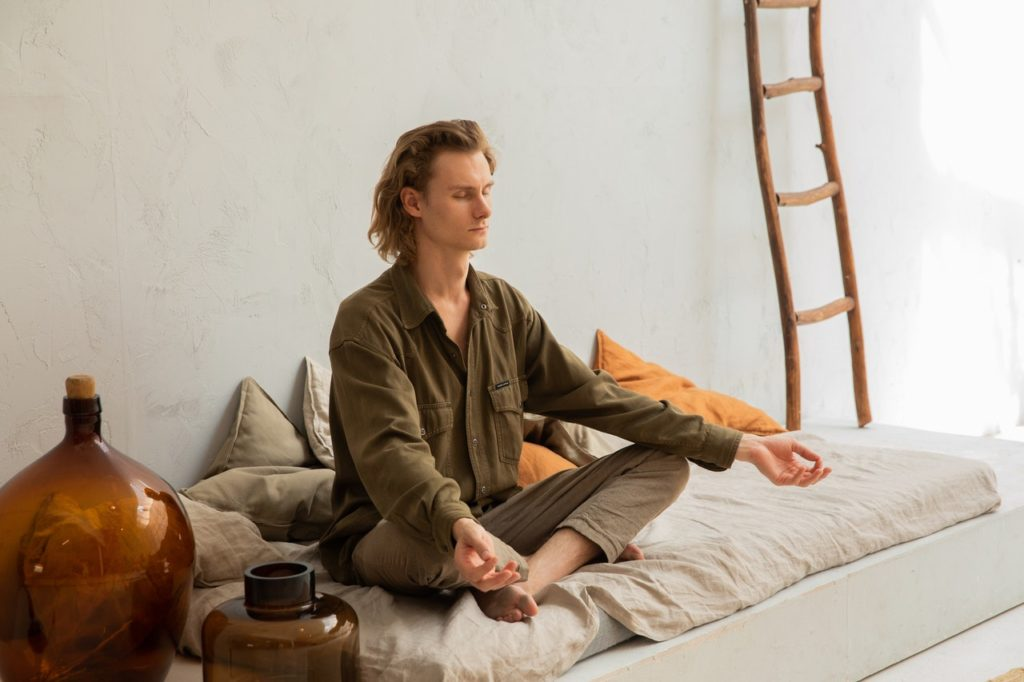 man meditating on his bed