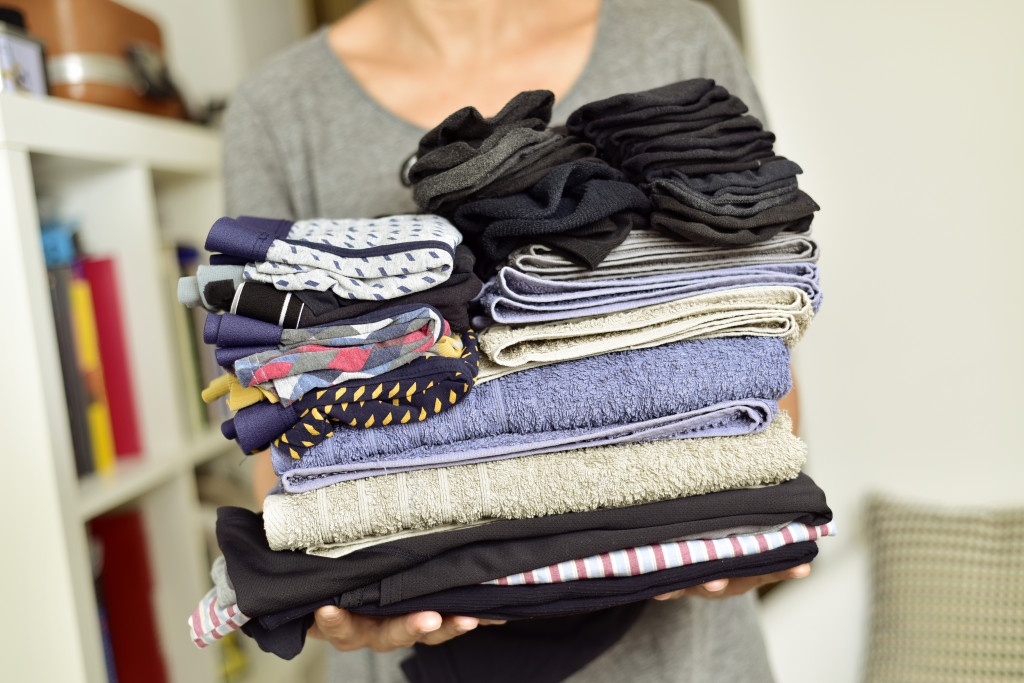 woman holding folded clothes
